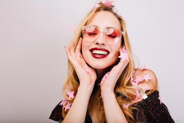 Nahaufnahmeporträt der fröhlichen blonden frau, die rosa brille trägt und lächelt, spaß an der party hat, mit geschlossenen augen genießt. hat langes lockiges haar, stilvollen look.