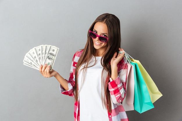 Nahaufnahmeporträt der fröhlichen jungen frau in den rosa gläsern, die einkaufstaschen und dollarbanknoten halten