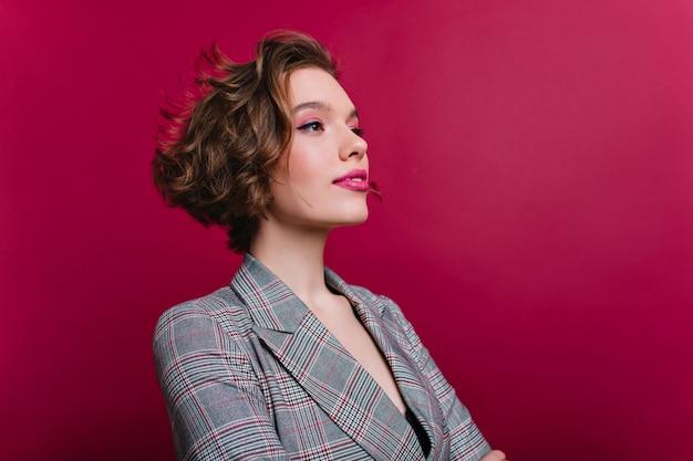 Nahaufnahmeporträt der frohen geschäftsfrau mit dem eleganten kurzen haarschnitt, der weg schaut. raffiniertes kaukasisches mädchen mit rosa make-up, das in grauer jacke auf rotweinwand aufwirft.