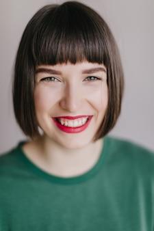 Nahaufnahmeporträt der glamourösen jungen frau mit grünen augen. lachendes weibliches modell mit dunklem haar isoliert.