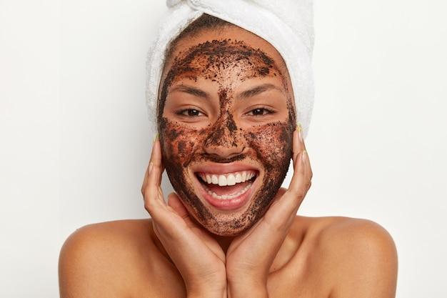 Nahaufnahmeporträt der glücklichen afroamerikanischen frau wendet kaffeemaske zur reinigung an, will erfrischt und gesund aussehen