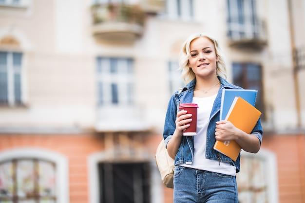 Nahaufnahmeporträt der glücklichen blonden studentin mit vielen in jeans gekleideten notizbüchern
