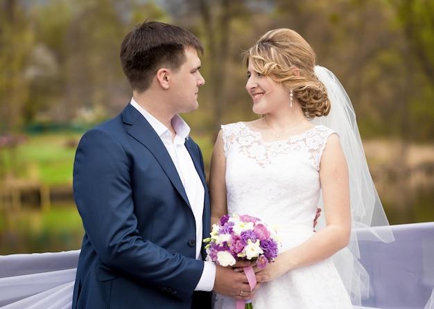 Nahaufnahmeporträt der glücklichen braut und des bräutigams, die händchen halten und sich ansehen