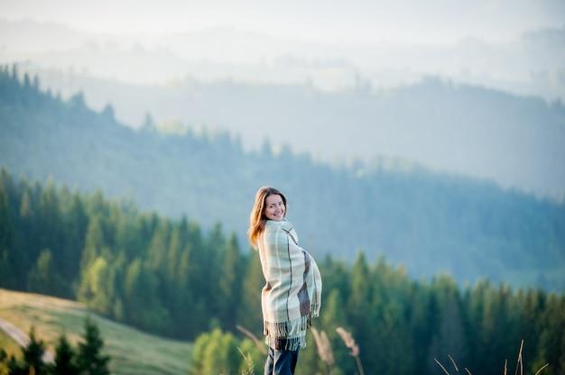 Nahaufnahmeporträt der glücklichen frau bedeckt mit einem plaid, das auf einem hügel gegen schöne berglandschaft mit morgendunst über den bergen und den wäldern steht
