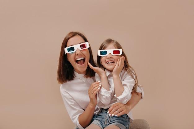 Nahaufnahmeporträt der glücklichen frau mit dem kleinen mädchen, das einen film in der 3d-brille mit überraschten emotionen ansieht