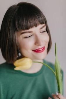 Nahaufnahmeporträt der glücklichen frau mit den roten lippen verträumt wegsehen, während sie mit blume aufwirft. schönes weißes mädchen, das gelbe tulpe mit inspiriertem lächeln hält.