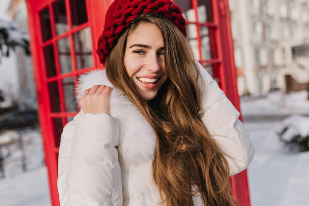 Nahaufnahmeporträt der glücklichen frau mit glänzendem braunem haar, das neben roter anrufbox aufwirft. foto im freien des atemberaubenden weiblichen modells in der gestrickten baskenmütze, die frostigen morgen in england genießt.
