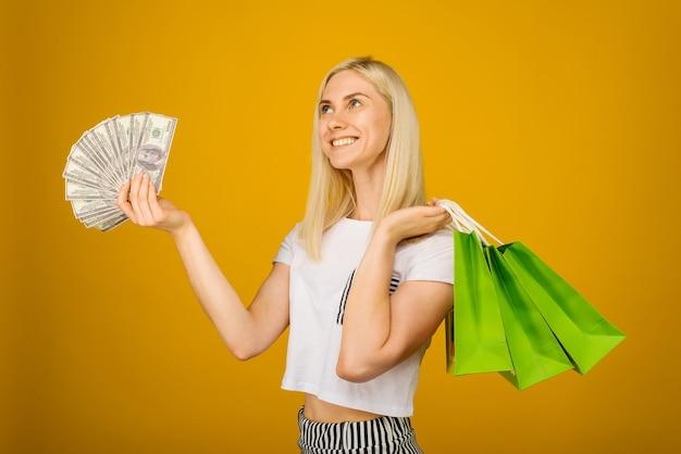 Nahaufnahmeporträt der glücklichen jungen schönen blonden frau, die geld und grüne einkaufstaschen hält, auf gelb
