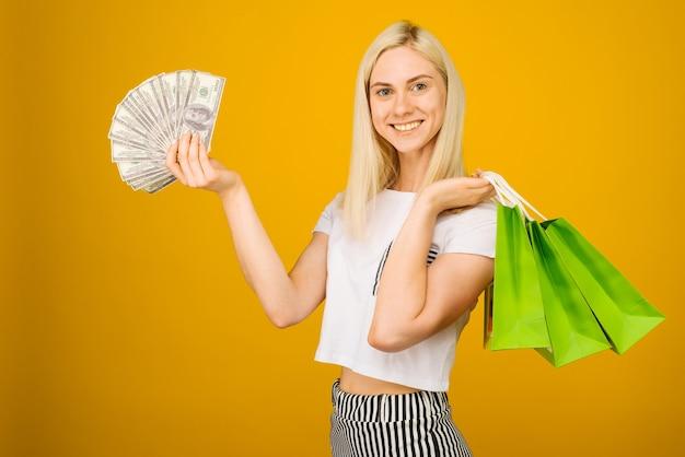 Nahaufnahmeporträt der glücklichen jungen schönen blonden frau, die geld und grüne einkaufstaschen hält, kamera betrachtend, auf gelb