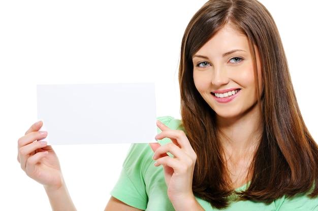 Nahaufnahmeporträt der glücklichen jungen schönen frau, die in den händen weiße leere karte hält