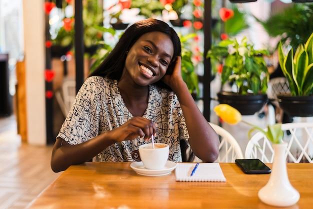 Nahaufnahmeporträt der glücklichen jungen schwarzen frau, die kaffee im café trinkt