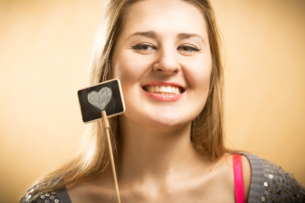 Nahaufnahmeporträt der glücklichen lächelnden frau, die kreidetafel mit gezeichnetem herzen hält