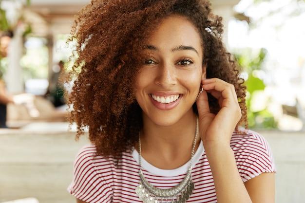 Nahaufnahmeporträt der glücklichen lächelnden frau mit breitem lächeln hat entzückenden ausdruck, ruht gegen caféinnenraum allein, ist gut gelaunt, hat pause nach hartem arbeitstag. positives emotionskonzept