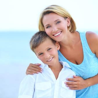Nahaufnahmeporträt der glücklichen mutter und des glücklichen sohnes in der umarmung am strand.