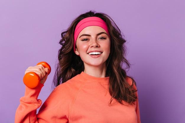 Nahaufnahmeporträt der grünäugigen lockigen frau im orangefarbenen pullover und im rosa sportstirnband