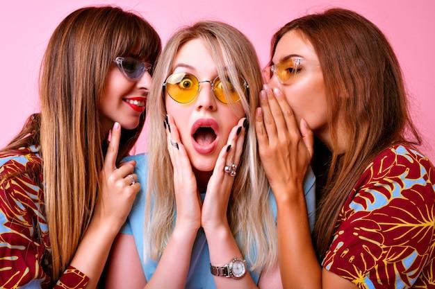 Nahaufnahmeporträt der gruppe lustige stilvolle frau, die geheimnisse miteinander flüstert, überraschte aufgeregte emotionen, trendige farblich passende kleidung und brille. glückliche freunde, die spaß haben