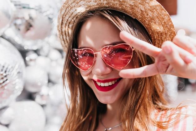 Nahaufnahmeporträt der gut gelaunten weißen frau, die mit friedenszeichen aufwirft. foto des entspannten schönen mädchens trägt hut und rosa sonnenbrille.