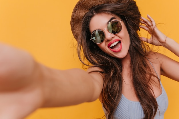 Nahaufnahmeporträt der gutaussehenden aufgeregten frau, die foto von sich selbst macht