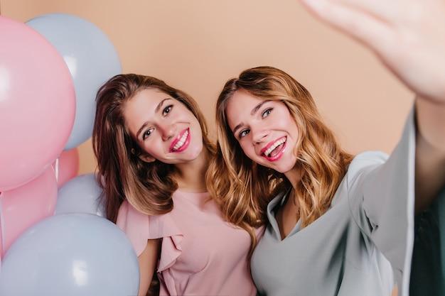 Nahaufnahmeporträt der gutaussehenden brünetten frau mit blauen luftballons