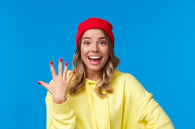 Nahaufnahmeporträt der gutaussehenden fröhlichen lächelnden frau in der roten mütze und im gelben kapuzenpulli, die nummer fünf oder fünften zeigt, bestellung aufgeben, plätze für freunde reservieren, auf einer blauen wand stehen