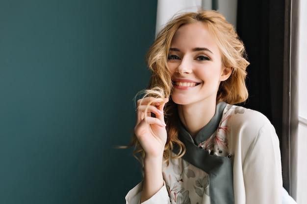 Nahaufnahmeporträt der herrlichen blonden jungen frau, die türkispyjamas trägt, sitzt neben dem fenster. sie ist glücklich, lächelt und berührt ihr welliges haar.