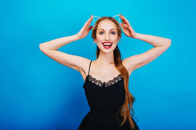 Nahaufnahmeporträt der herrlichen blondine bereit für partei, lächelndes und berührendes stirnband mit katzenohr in diamanten tragen des schönen schwarzen kleides, helles make-up.
