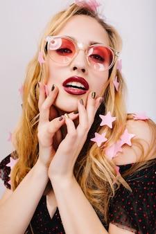 Nahaufnahmeporträt der herrlichen blondine, die auf der party sexy aussieht, bedeckt mit sternkonfetti, sinnlich berührendes gesicht. trägt eine rosa trendige brille, hat langes lockiges haar, rote lippen und eine stilvolle maniküre. isoliert..