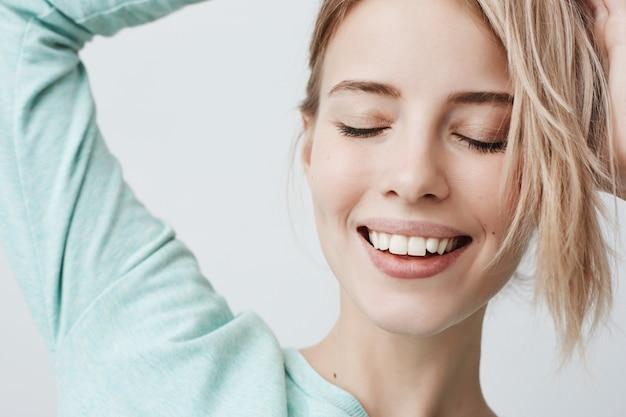 Nahaufnahmeporträt der herrlichen freudigen blonden frau mit zarten merkmalen, stellt gegen graue wand auf, lächelt brodly, zeigt weiße zähne und vollkommen reine haut. schöne frau mit geschlossenen augen
