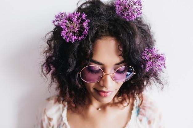 Nahaufnahmeporträt der hübschen afrikanischen frau in der sonnenbrille, die mit geschlossenen augen aufwirft. wundervolles weibliches modell mit dunklem haar, das mit lila blumen isoliert wird.
