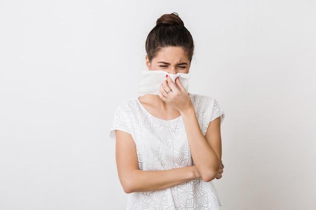 Nahaufnahmeporträt der hübschen frau, die ihre nase mit serviette putzt, sich erkältet, sich krank, isoliert, stirnrunzelnd fühlt