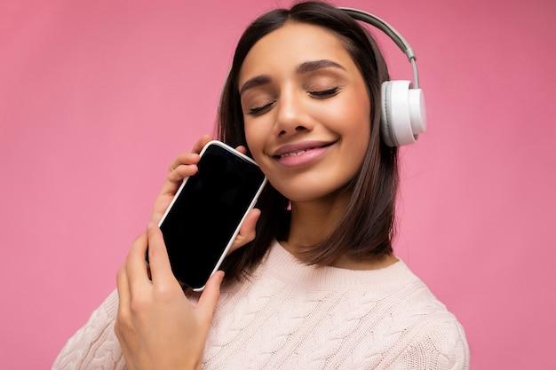Nahaufnahmeporträt der hübschen jungen brünetten frau, die rosa lässigen pullover trägt, isoliert über rosa