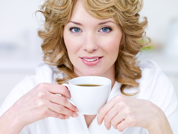 Nahaufnahmeporträt der hübschen jungen schönen blonden frau mit tasse kaffee
