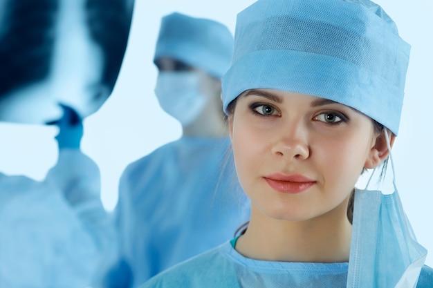 Nahaufnahmeporträt der jungen ärztin des chirurgen, umgeben von ihrem team