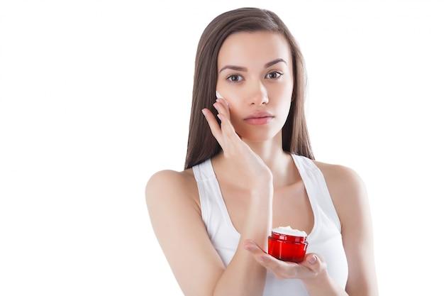 Nahaufnahmeporträt der jungen attraktiven frau, die gesichtscreme anwendet. frau, die ein glas mit feuchtigkeitsspendender gesichtscreme hält.