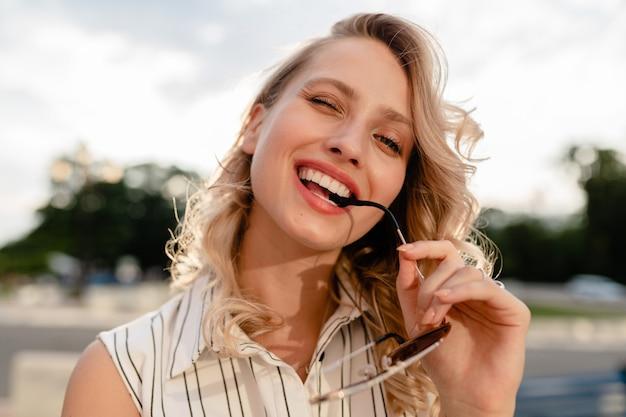 Nahaufnahmeporträt der jungen attraktiven stilvollen blonden frau in der stadtstraße im sommermodeartkleid, das sonnenbrille hält
