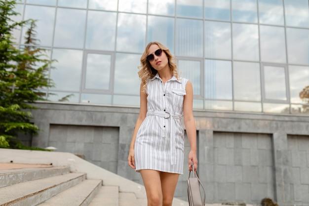 Nahaufnahmeporträt der jungen attraktiven stilvollen blonden frau in der stadtstraße im sommermodeartkleid, das sonnenbrille trägt