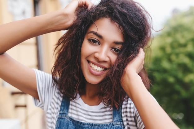 Nahaufnahmeporträt der jungen frau der brünette mit bronzehaut, die mit vergnügen im freien und lächelnd aufwirft