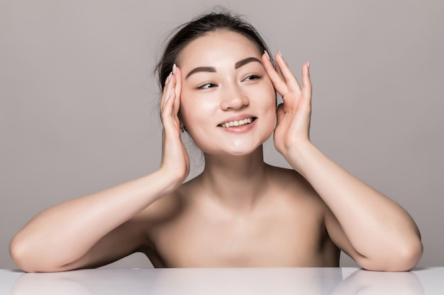 Nahaufnahmeporträt der jungen frau gesicht hautpflege mit kosmetik lokalisiert auf grauer wand