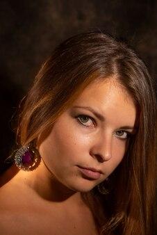 Nahaufnahmeporträt der jungen frau im gemischten licht gegen dunklen hintergrund