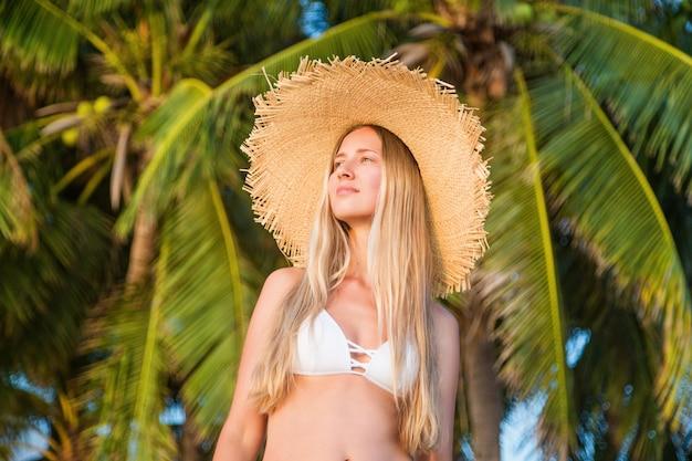 Nahaufnahmeporträt der jungen frau im großen strohhut, schöne frau, die tropisches sonniges wetter, recht gesundes entspannendes mädchen genießt. nahaufnahmeporträt von glücklichen jungen