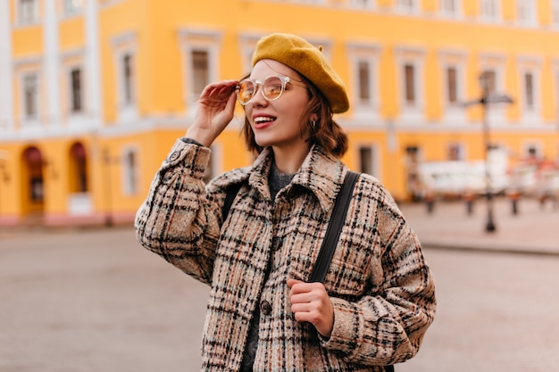 Nahaufnahmeporträt der jungen frau in der sonnenbrille, die stadtbild bewundert