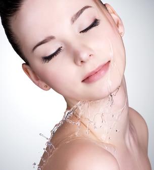 Nahaufnahmeporträt der jungen frau mit wassertropfen auf ihrem schönen gesicht