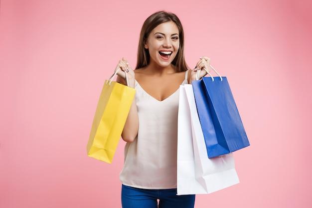 Nahaufnahmeporträt der jungen glücklichen frau, die taschen beim einkaufen hält