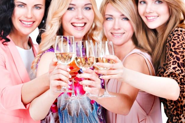 Nahaufnahmeporträt der jungen glücklichen frauen haben partei und wein trinken - lokalisiert auf weiß