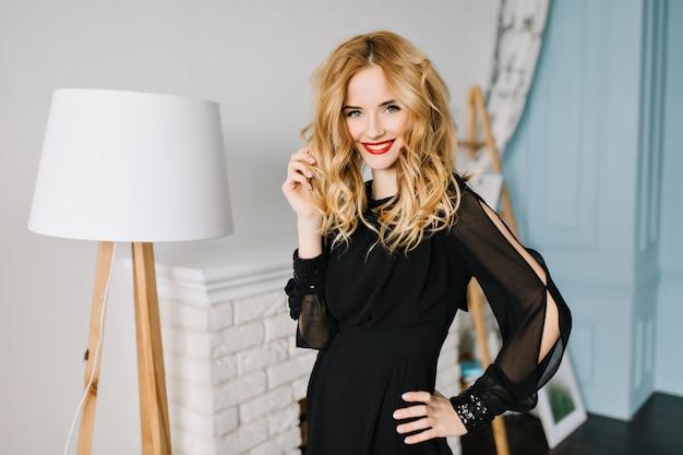 Nahaufnahmeporträt der jungen herrlichen frau, die stilvolles schwarzes kleid im gemütlichen raum trägt und ihr welliges haar berührt. kamin mit brennholz, weiße lampe