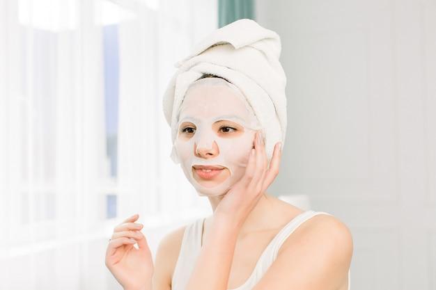 Nahaufnahmeporträt der jungen hübschen frau, die papierblattmaske auf ihrem gesicht anwendet. kosmetischer eingriff. beauty spa und kosmetologie.