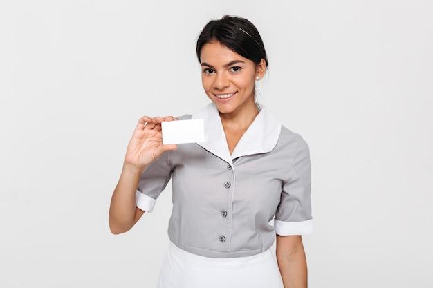Nahaufnahmeporträt der jungen lächelnden brünetten frau in der dienstmädchenuniform, die leere zeichenkarte hält