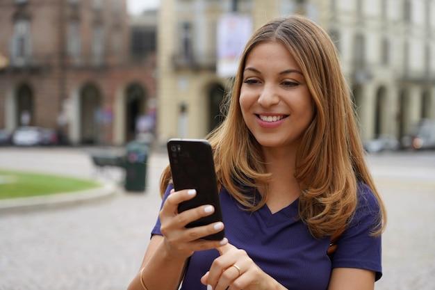 Nahaufnahmeporträt der jungen lächelnden frau, die draußen smartphone benutzt