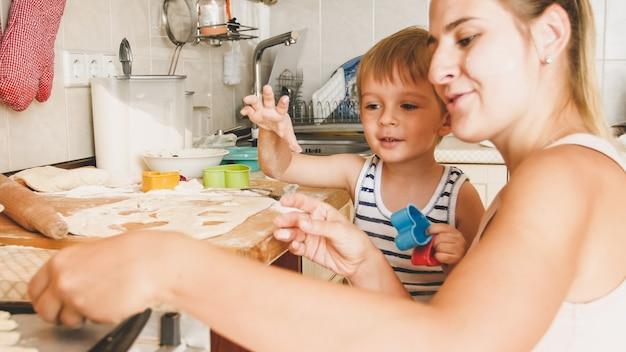 Nahaufnahmeporträt der jungen mutter mit dem kleinkindjungen, der eine backform hält und kekse in der küche macht
