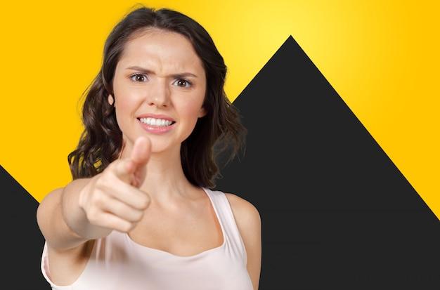 Nahaufnahmeporträt der jungen recht unglücklichen, ernsten frau, die auf jemand zeigt, als ob zu sagen, dass sie etwas falsch taten